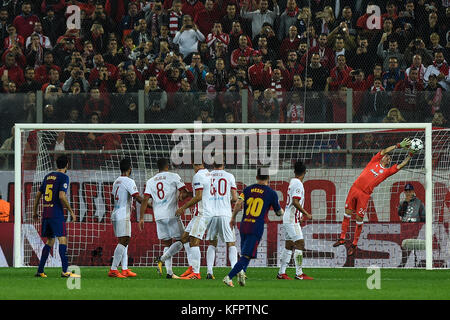 Athens, Greece. 31st Oct, 2017. Olympiacos goalie Silvio Proto (r) voparries a free kick by Lionel Messi (3.f.r) - Stock Photo