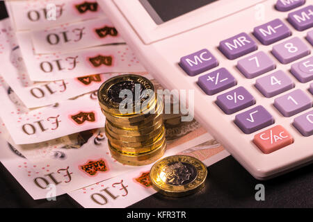 Calculator on new polymer sterling £10 ten pound notes and new pound coins. Concept of calculating British money - Stock Photo