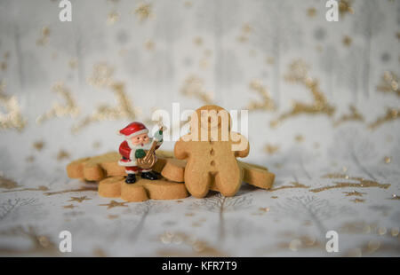 Christmas food photography image with mini ginger bread man biscuits and music santa claus decoration with gold - Stock Photo