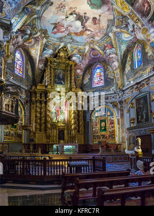 Woman sitting on pew in front of altar inside the Church of San Nicolas (Parroquia de San Nicolas), Ciutat Vella, - Stock Photo