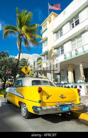 MIAMI - July 23, 2017: Classic vintage american car parked on Miami Beach's iconic Ocean Drive with backdrop of - Stock Photo
