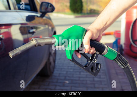 Man hand holding gasoline pump in a gas station ready to fill the tank or to refuel as expensive fuel concept with - Stock Photo