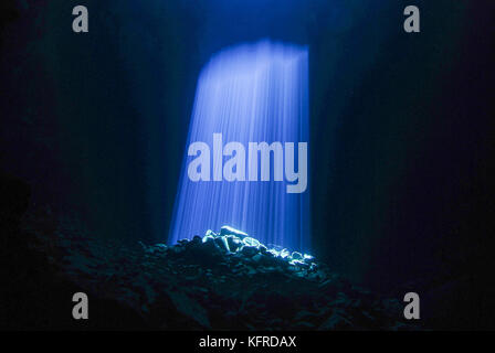 Blue Sunlight shining through hole in underwater cave - Stock Photo