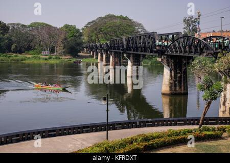 Tourist boat about to pass under The River Kwai Bridge, Kanchanaburi, Thailand - Stock Photo