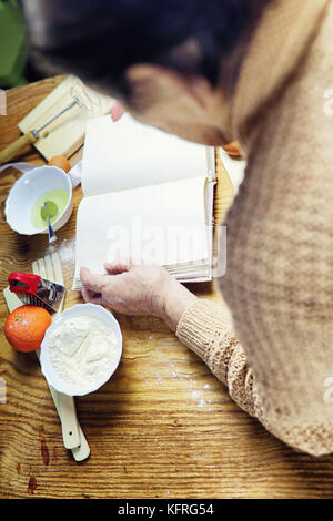 Open recipe book in the hands of an elderly woman - Stock Photo