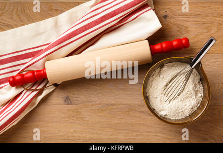 Kitchen table counter countertop with cooking utensils wooden rolling pin and cotton dish towel dishtowel, and baking - Stock Photo