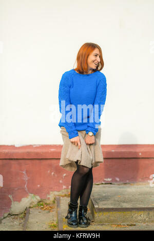 A beautiful young woman with red hair in a blue sweater made of natural wool and woolen beige skirt smiling and - Stock Photo