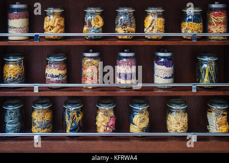 On the wooden shelves are glass jars with various varicoloured types of pasta, spaghetti, beans, cereals for their - Stock Photo