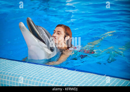 A cheerful red-haired woman in a red bathing suit laughs, bathes and holds a dolphin in the blue pool behind her - Stock Photo