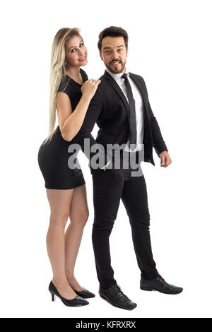 Elegant couple poses for the photos. They are dressed for a wedding, social event. Elegant and black clothes. - Stock Photo
