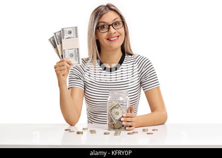 Young woman with bundles of cash and a jar filled with money sitting at a table isolated on white background - Stock Photo
