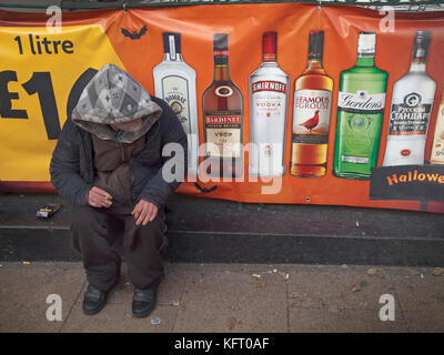 A rough sleeper sits on the pavement by adverts for alcohol in Brighton - Stock Photo