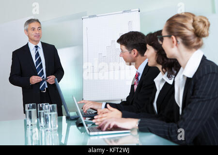 Cropped view image of a row of businesspeople working on laptops and tablets during a presentation or meeting - Stock Photo