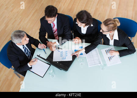 Overhead view of a group of diverse business executives holding a meeting around a table discussing graphs showing - Stock Photo