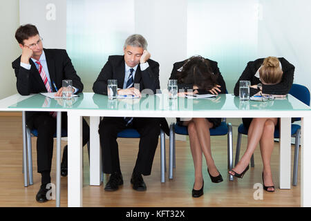 Bored panel of professional judges or corporate interviewers lounging around on a table napping as they wait for - Stock Photo