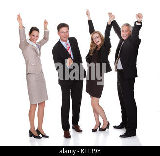 Four excited diverse professional businesspeople celebrating a success laughing and raising their arms in the air - Stock Photo