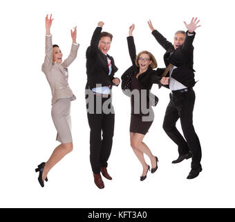 Four diverse professional business partners jumping for joy with their arms raised shouting in jubilation isolated - Stock Photo