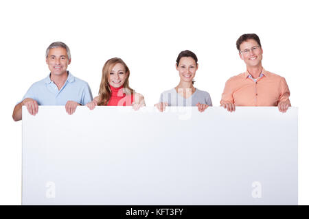 Two happy attractive middle-aged couples in casual clothing holding up a blank horizontal board or banner isolated - Stock Photo