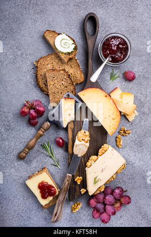 Assorted cheeses on wooden board - Stock Photo
