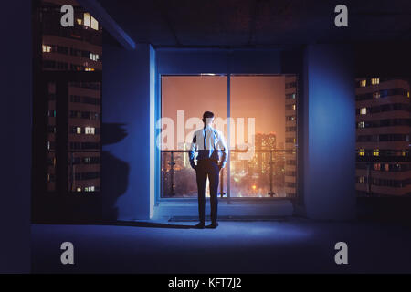 Office worker or employee is standing near big window at the night time. Overstay concept - Stock Photo