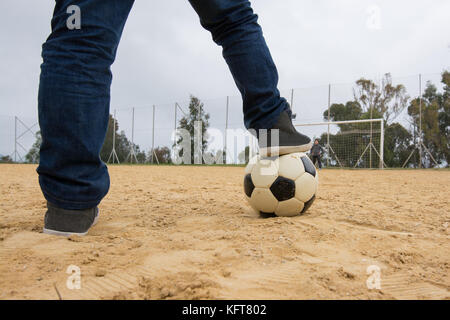 Little boy  with his foot resting on top of a soccer ball on sand of a old field - Stock Photo