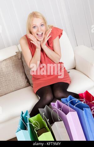 Beautiful young woman checking her shopping bags - Stock Photo