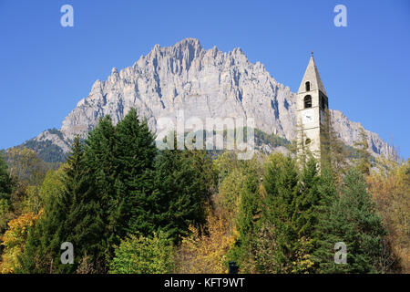 BELL TOWER WITH A MASSIVE CLIFF FOR BACKDROP. Sambuco, Province of Cuneo, Piedmont, Italy. - Stock Photo