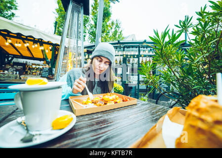 Beautiful woman eating in outside cafe - Stock Photo