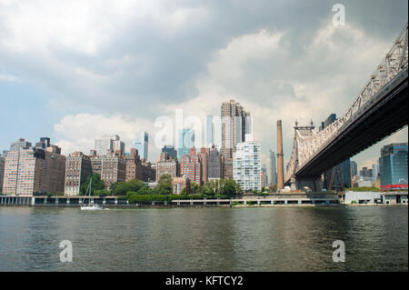 New York City and Queensboro Bridge skyline viewed across the East River from Roosevelt Island waterfront. - Stock Photo