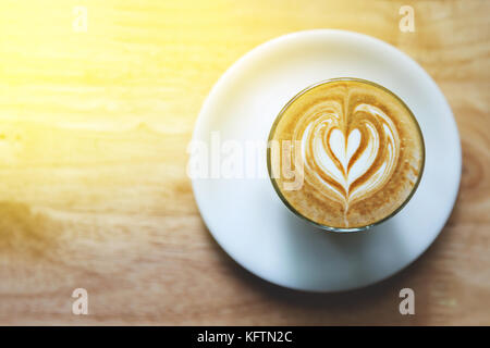 heart drawing on latte art coffee on wood table background - Stock Photo