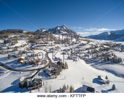 Fresh snow covers the homes and yards of Mount Crested Butte, Colorado with the ski area of Crested Butte Mountain - Stock Photo