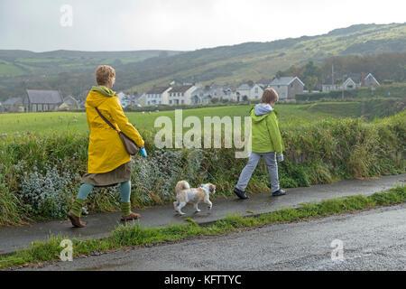 family walking dog, Ballintoy, Co. Antrim, Northern Ireland - Stock Photo
