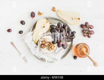 Camembert cheese with grape, walnuts, pear and honey on vintage metal plate - Stock Photo