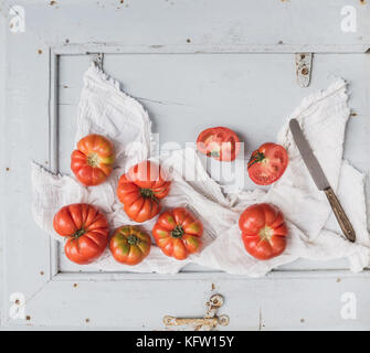 Fresh ripe hairloom tomatoes in rustic blue wooden tray  - Stock Photo