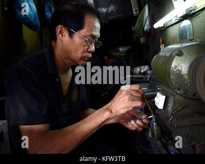 ANTIPOLO CITY, PHILIPPINES - OCTOBER 27, 2017: A worker sharpens a nipper in his repair shop. - Stock Photo