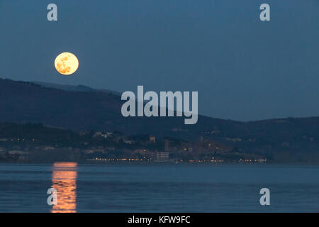 Beautiful view of full moon just over Passignano (Umbria), reflecting on the water of Trasimeno lake - Stock Photo