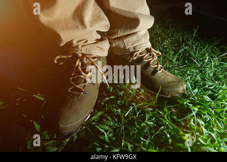 Close-up of pair hiking shoes stand on green grass. Outside walking boots - Stock Photo