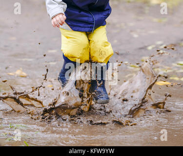 Happy two years old boy jumping on muddy puddles in rubber boots - Stock Photo