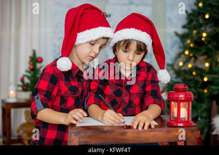 Two adorable children, boy brothers, writing letter to Santa Claus at home - Stock Photo