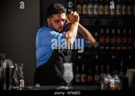 The bartender shakes and mixing alcohol cocktail - Stock Photo