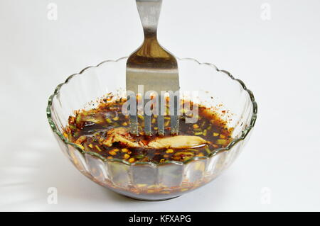 roast chicken stab on fork dressing in spicy sauce - Stock Photo