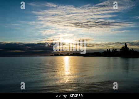 Beautiful sunrise over lake. The rising sun shines through dramatically clouds, silhouette of trees on the shore - Stock Photo