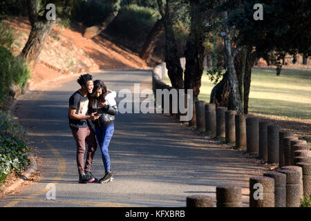 Couple looking at a cellphone whilst walking down a road - Stock Photo