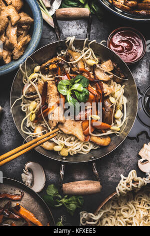 Asian dish with chicken vegetables noodle stir-fry in little wok with chopstick and cooking ingredients, top view - Stock Photo