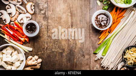 Asian vegetarian cooking ingredients for stir fry with tofu, noodles , vegetables and sauces on wooden rustic background, - Stock Photo