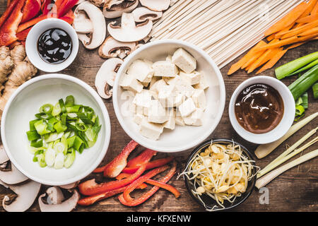 Top view of Asian vegetarian cooking ingredients for stir fry with tofu, noodles and vegetables - Stock Photo