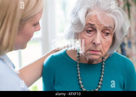 Care Worker Talking To Depressed Senior Woman At Home - Stock Photo