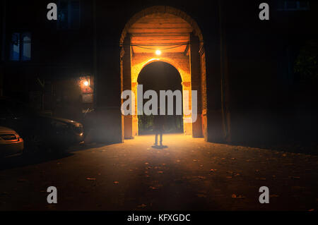 man stand alone at the foggy street under the street arch of the old house - Stock Photo