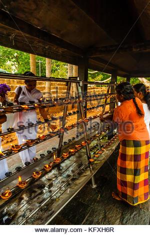 Buddhist Pilgrims lighting oil lamps outside the Sri Maha Bodhi. The sacred bodhi tree. Anuradhapura, North Central, - Stock Photo