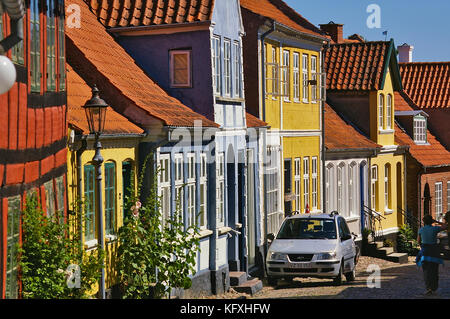 Aeroskobing, Denmark - July 4th, 2012 - Narrow cobblestone street on the island of Aero with colorful historic residential - Stock Photo